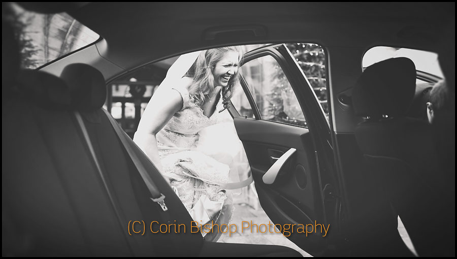 Bride laughing getting into the car