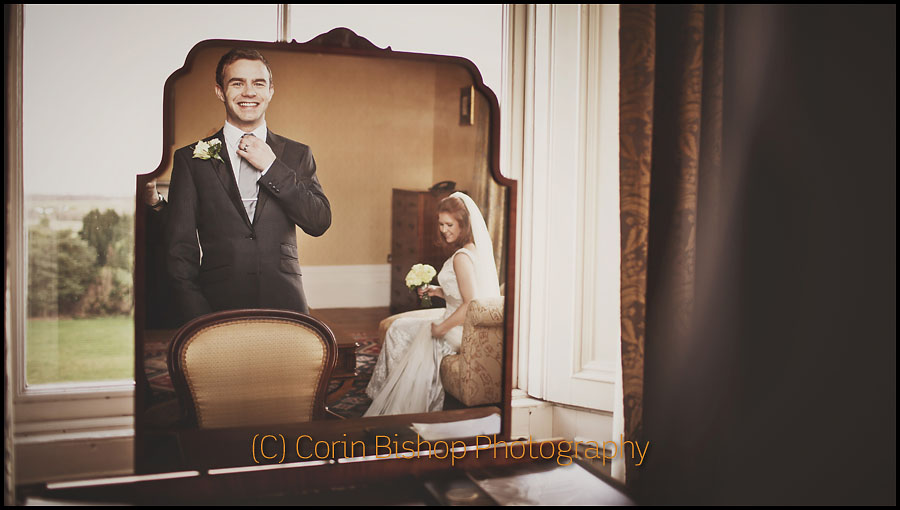Groom in the mirror. Bride in the background