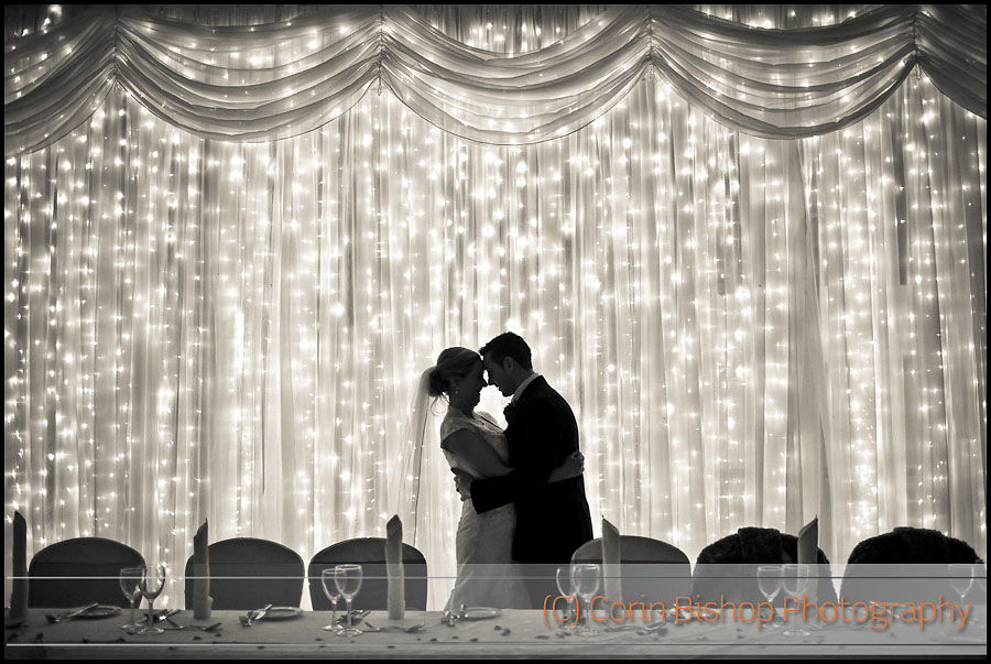 Bride and Groom Kissing Silhouetted Against Lights