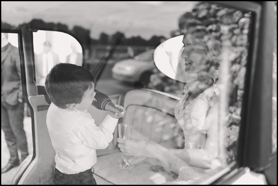 Bride and Grooms Son serves up the champagne in the car