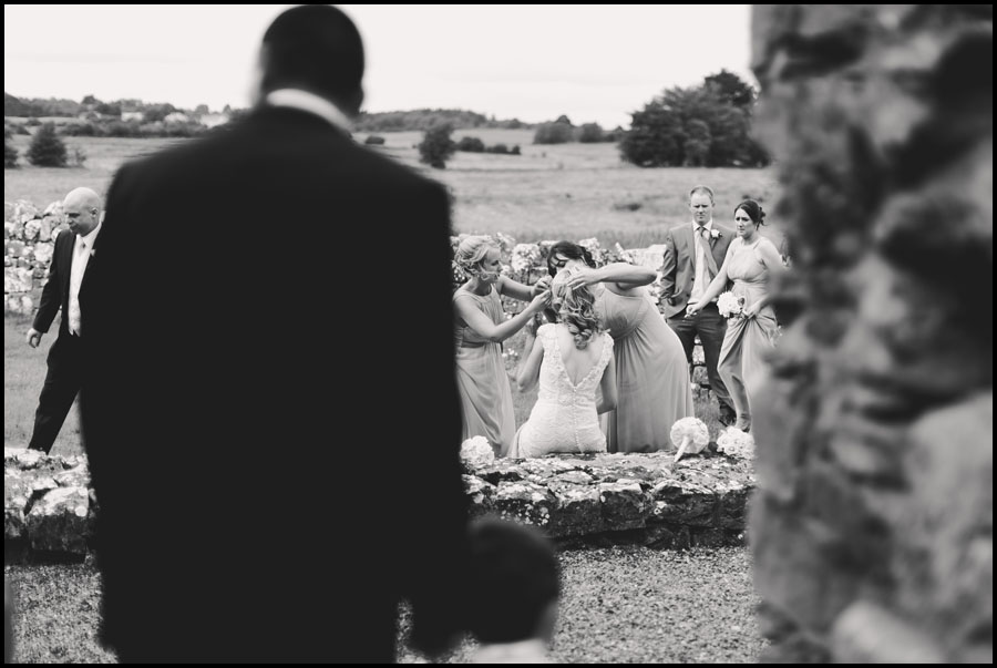 Groom waits while the bride gets some last minute adjustments to her hair