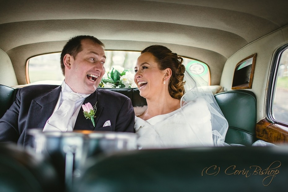 Bride and groom having a laugh in the silver rolls royce wedding car