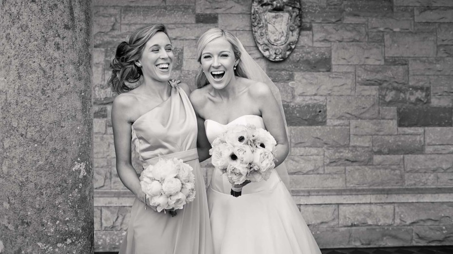 bride and her sister sharing a laugh at her wedding