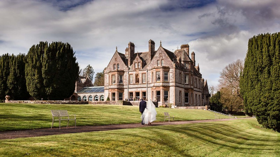 Happy wedding couple with the Castle Leslie Estate house in the background