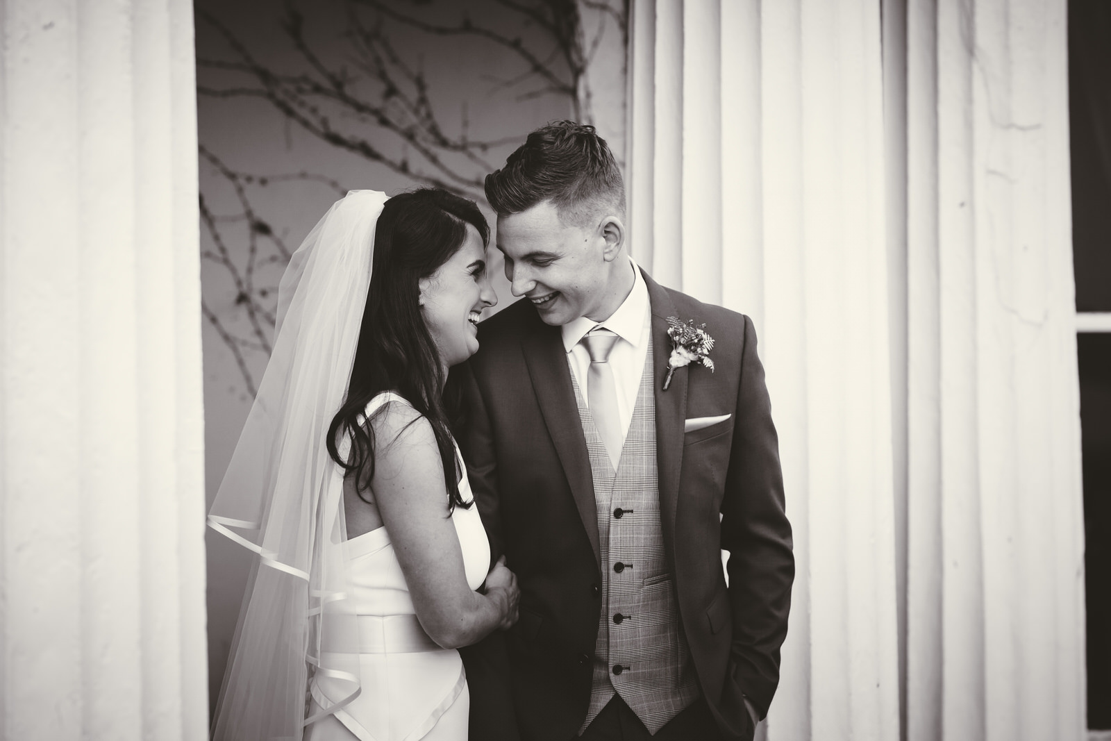 A shared happy moment between the bride and groom in black and white